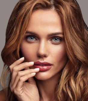 自然化粧と完璧な肌のポーズを持つ若いブロンドの女性モデルの美容ファッションの肖像画。彼女の口に触れる