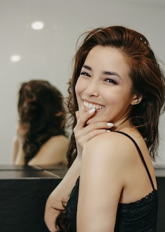 Beauty fashion portrait of sensual smiling asian young woman with dark long hair in front of mirror