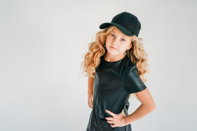 Beauty fashion portrait of smiling curly hair tween girl in black leather dress and baseball cap on the white  isolated