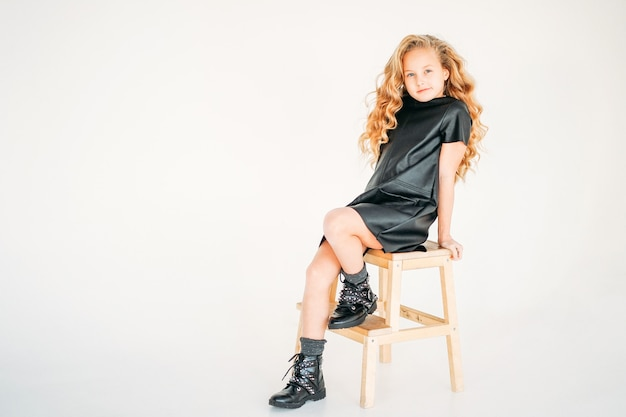 Beauty fashion portrait of smiling curly hair tween girl in black leather dress and on white