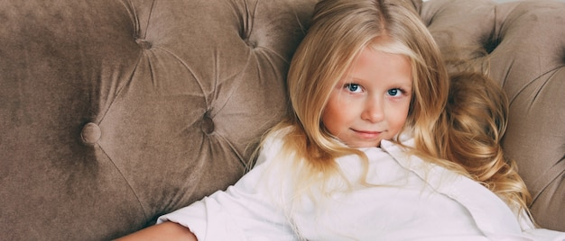Beauty fashion portrait of smiling little tween girl with fair long hair in white shirt on beige sofa background banner, children's modeling