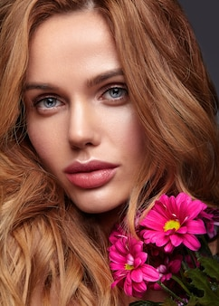 Beauty fashion portrait of young blond woman model with natural makeup and perfect skin with bright сrimson chrysanthemum flower posing