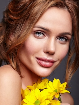 Beauty fashion portrait of young blond woman model with natural makeup and perfect skin with bright yellow chrysanthemum flower posing