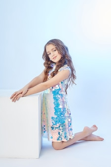 Beauty fashion portrait of a young girl in a dress on a light background