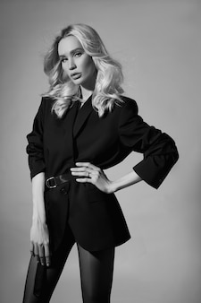 재킷과 스타킹에 뷰티 패션 섹시한 여자, 긴 다리를 가진 금발 소녀. 모델의 완벽한 모습, 회색 배경에 있는 여성의 초상화