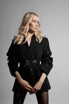 Красота моды сексуальная женщина в куртке и колготках, белокурая девушка с длинными ногами. идеальная фигура модели, портрет женщины на сером фоне