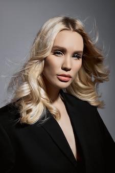 美容ファッションセクシーな女性のジャケットとタイツ、長い脚を持つブロンドの女の子。モデルの完璧な図、灰色の壁に女性の肖像
