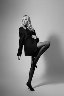 Красота моды сексуальная женщина в куртке и колготках, блондинка с длинными ногами