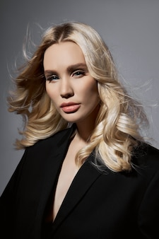 ジャケットとタイツの美容ファッションセクシーな女性、長い脚を持つブロンドの女の子。モデルの完璧な図、灰色の背景に肖像画の女性