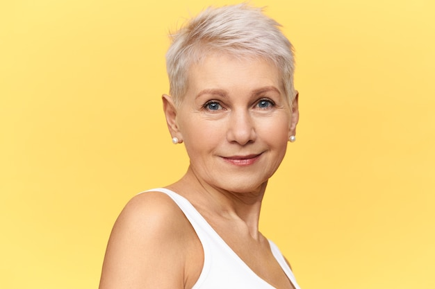 Beauty, fashion, style, femininity and aging concept. portrait of stylish confident middle aged european female with beautiful neat skin, blue eyes and pixie haircut posing isolated, smiling