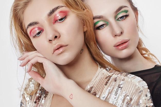 Красота мода две женщины с ярким макияжем на лице