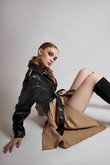 트렌치 코트를 입은 뷰티 패션 젊은 여성, 전문적인 얼굴 화장 소녀. 흰색 바탕에 여자의 초상화입니다. 비오는 날씨에 봄옷