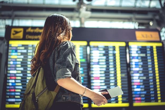時間を離れることを確認するための飛行スケジュールを見ている美容女性観光客