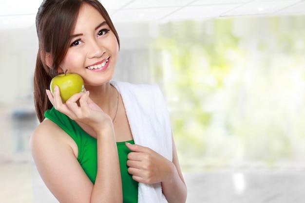 Beauty fitness woman eating fresh green apple