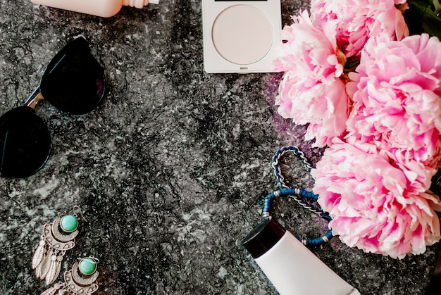 Beauty flat lay with accessories, perfume, cosmetics and peonies on a dark marble background