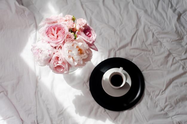 Красота плоская лежала с кофе и букетом цветов розы и пионов
