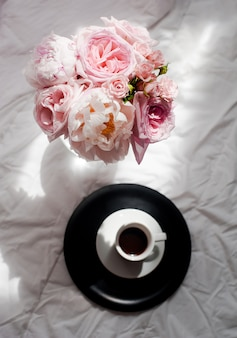 Beauty flat lay with coffee and bouquet of flower roses and pions