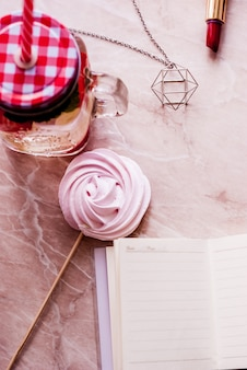 Beauty flat lay with a diary, accessories, lipstick, merengue and jar with water on a marble background