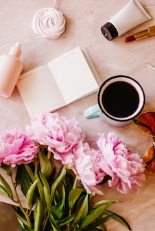 Beauty flat lay with a diary, cup of coffee, accessories and peonies on a marble background