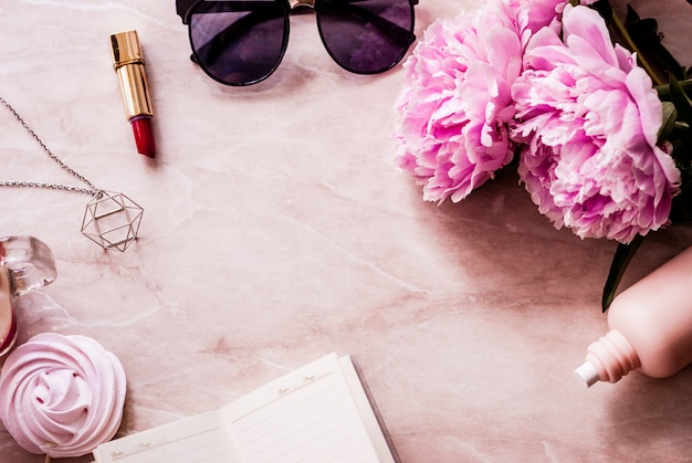 Beauty flat lay with a diary, smartphone, accessories and peonies on a marble background