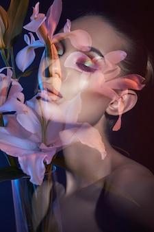 二重露光の女性の美花顔。女の子のネオンの光と色の肖像画、プロのメイク、女性の裸の背中、頭の中の花
