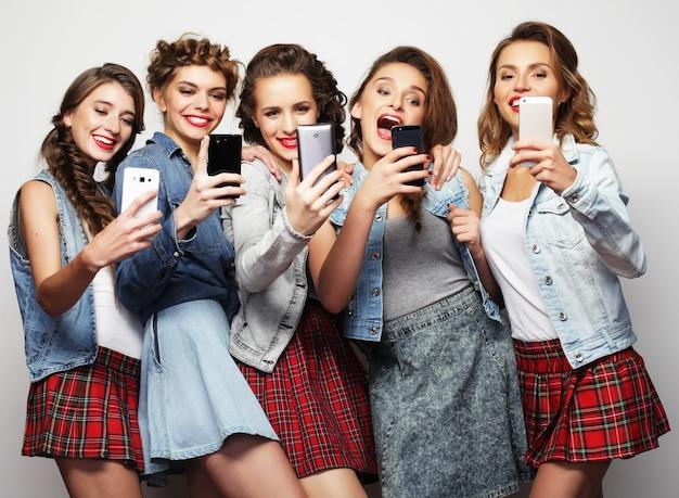 美しさ、友情、若さとテクノロジー。自撮りをしている5人のゴージャスな若い女性のスタジオポートレート。