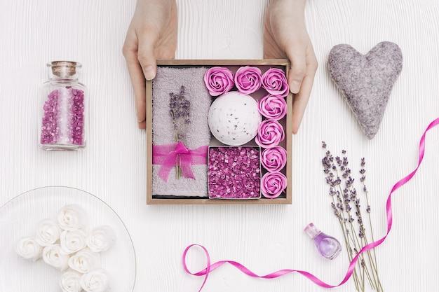 아름다움 선물 상자. 스파 라벤더 꽃과 라벤더 오일, 목욕 폭탄, 바다 소금, 목욕 장미, 회색 수건으로 집에서 휴식을 취하십시오.