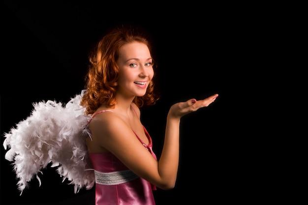Ангел красоты девушка в розовом на черном фоне