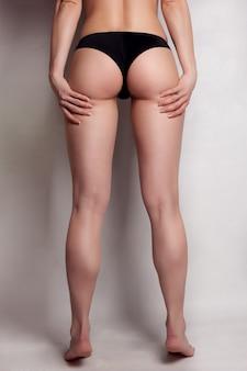 灰色の背景に分離されたズボンの美しさの少女