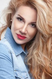 デニムの白い背景の上の美しさの少女ゴージャスな髪の肖像画