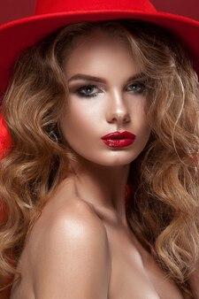 손에 빨간 크리스마스 모자와 전나무 나무에 아름다움 여자. 깨끗한 피부, 화사한 메이크업, 빨간 립스틱, 빨간 머리 색깔