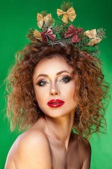 손에 빨간 크리스마스 모자와 전나무 나무에 아름다움 여자