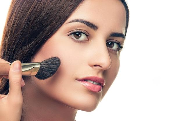 Красавица, делающая макияж кистью