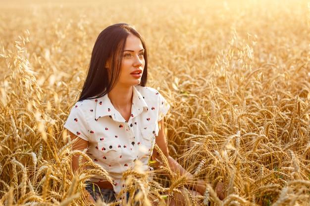야외에서 밀밭에 자연을 즐기는 뷰티 소녀 황금 fi에 긴 머리를 가진 아름 다운 모델 소녀.