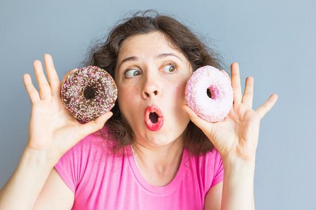 カラフルなドーナツを取る美女。お菓子、デザートと面白い楽しい女性。ダイエット、ダイエットのコンセプト。ジャンクフード、お祝い、パーティー。