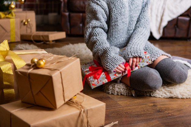 Beauty girl in a warm dress sits on a rug and ties a gift with a ribbon for the new year near other boxes with gifts in the room
