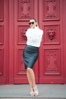 Девушка красоты с взглядом очарования. женщина в туфлях на высоком каблуке на красной двери в париже, франция. сексуальная женщина в солнечных очках с длинными волосами. фотомодель с модным стилем. мода, красота и мода.