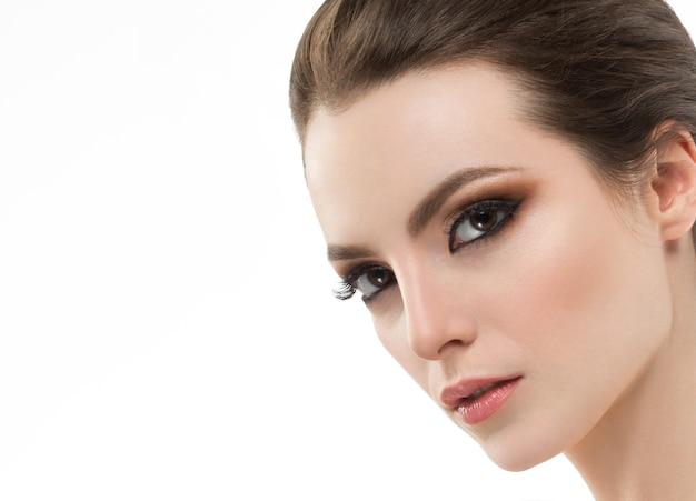 아름다움 여자 여자 얼굴 초상화입니다. 아름다운 스파 모델 소녀 완벽한 신선한 깨끗한 피부. 웃 고 갈색 머리 여성입니다. 얼굴 피부를 만지는 손 젊음과 피부 관리 개념. 격리 된 흰색 배경입니다. 스튜디오 쉬