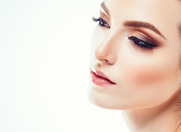 아름다움 여자 여자 얼굴 초상화입니다. 아름다운 스파 모델 소녀 완벽한 신선한 깨끗한 피부. 웃 고 갈색 머리 여성입니다. 얼굴 피부를 만지는 손 젊음과 피부 관리 개념. 격리 된 흰색 배경