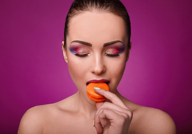 Beauty glamor fashion model girl with colourful makeup and macaroon