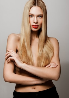Beauty glamour fashion model portrait with shiny blonde hairstyle with red lips on grey background. wearing black pants