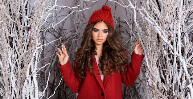 서리가 내린 겨울 공원에서 아름다움 매력적인 여자. 빨간 니트 모자, 물결 모양의 놀라운 헤어 스타일, 전체 입술과 밝은 메이크업에 아름 다운 젊은 여자.