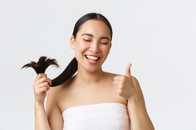 Красота, продукты от выпадения волос, шампунь и концепция ухода за волосами. крупный план довольной, счастливой азиатской девушки в банном полотенце, показывая большие пальцы руки и кончики здоровых волос, стоящую довольную белую стену.