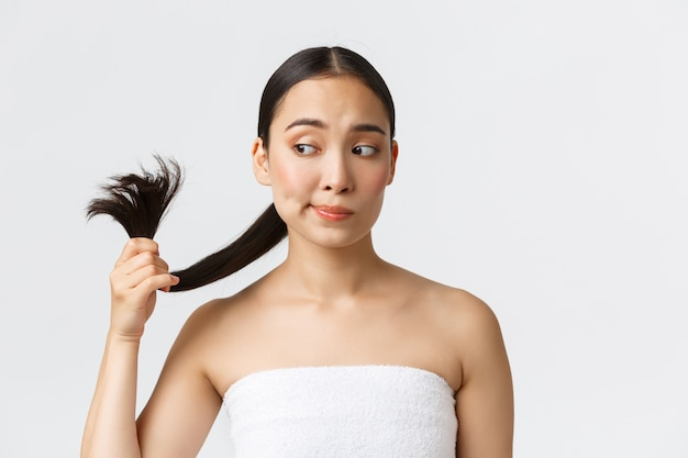 Красота, продукты от выпадения волос, шампунь и концепция ухода за волосами. обеспокоенная красивая азиатская женщина в полотенце ванны смотря секущиеся концы, нуждается в обработке волос, стоя белой стене.