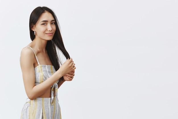 美容、ヘアスタイル、ヘアケアのコンセプト。きれいな肌、髪の毛に触れ、優しい笑顔で見つめ、灰色の壁の上に立っている優しい魅力的な若い女性の肖像画