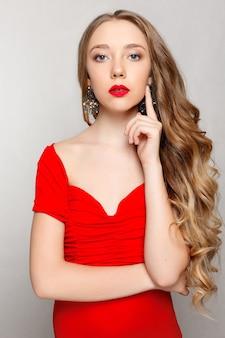 美しさ、髪型、人々のコンセプト-長いカールした髪の美しいモデルのブルネット。女の子の大きなネックレスビーズとチェーン。ジュエリーとアクセサリー。ヘアスタイルの波状のカール。赤いドレスと宝石の女の子