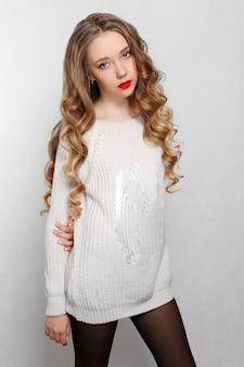 美しさ、髪型、人々のコンセプト-長いカールした髪の美しいモデルのブルネット。ビーズとチェーンの女の子の大きなネックレス。ジュエリーとアクセサリー。ヘアスタイルの波状のカール。女の子の白い長いセーター