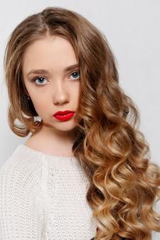 美しさ、髪型、人々のコンセプト-長いカールした髪の美しいモデルのブルネット。ビーズとチェーンの女の子の大きなネックレス。ジュエリーとアクセサリー。ヘアスタイルの波状のカール。女の子の白い長いセーター Premium写真