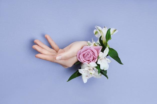 Красота рука с цветами в дыре в фиолетовой бумаге