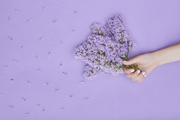 Beauty hand of a woman with blue flowers lies on table on purple paper